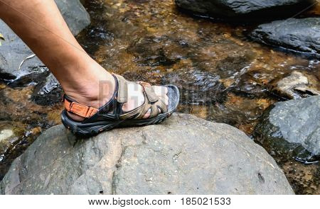 Trekking sandals on the rock in water steam concept trekking and hiking trip.