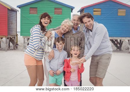 Portrait of happy multi-generation family standing against beach huts