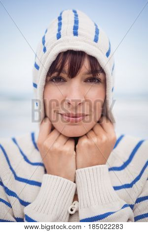 Close up portrait of woman wearing hooded sweater at beach during winter