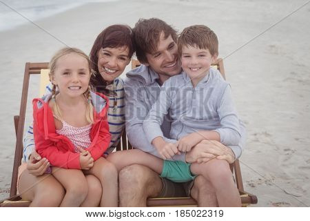 Happy family resting on lounge chairs at beach