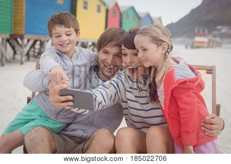 Cheerful family taking selfie while sitting on lounge chair at beach