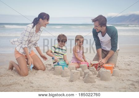 Happy family making sand castle at beach