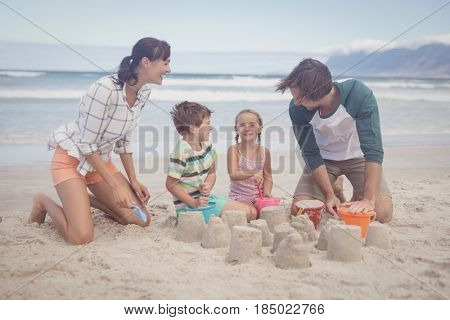Happy siblings with parents making sand castle at beach