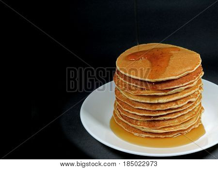 Stack of fresh homemade pancakes with maple syrup served on white plate, black background with free space for text or design