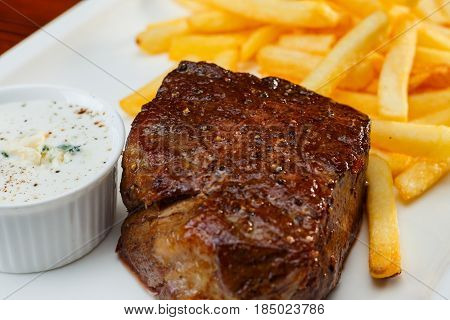 Rustic grilled beefsteak with french fries and garlic sauce. Close up.