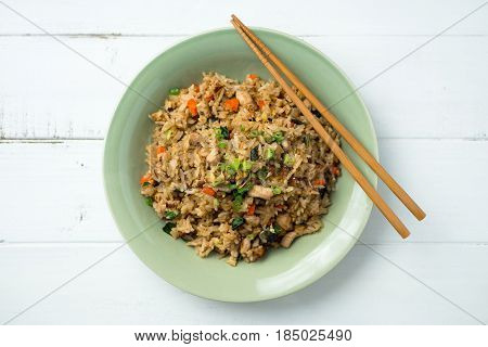 Fried rice top view. Basil chicken fried rice with chopsticks on a white wooden background viewed from above. This thai inspired meal is perfect for a quick lunch or served as side dish.