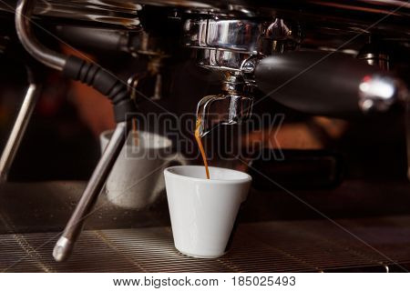 Coffee machine in a cafe pours fresh espresso in a porcelain cup