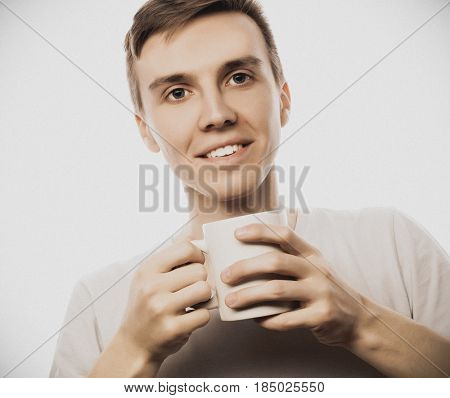 young man holding white cup with coffee