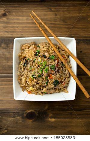 Chicken fried rice. Basil chicken fried rice with chopsticks on a wooden background viewed from above. This thai inspired meal is perfect for a quick lunch or served as side dish.