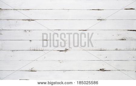 Distressed white wood texture background viewed from above. The wooden planks are stacked horizontally and have a worn look. This surface would be great as design element for a wall floor table etc...