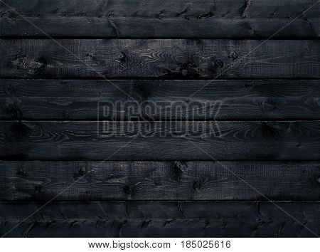 Dark black wood texture background viewed from above. The wooden planks are stacked horizontally and have a worn look. This surface would be great as design element for a wall floor table etc...