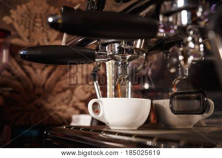 Coffee machine in a cafe pours fresh cappuccino in a porcelain cup