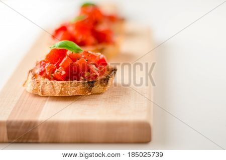 Fresh bruschetta appetizers. Bruschetta is an italian food made of chopped tomatoes garlic basil and fresh herbs on a toasted bread. These are traditionally served as snacks or antipasti (appetizers).