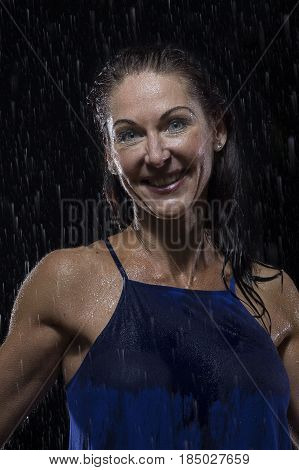 Beautiful woman in blue dress stands in rain at night getting wet