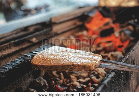 Luleh kebab (minced meat on spits, Middle Eastern staple) being fried on charcoal grill, toned image