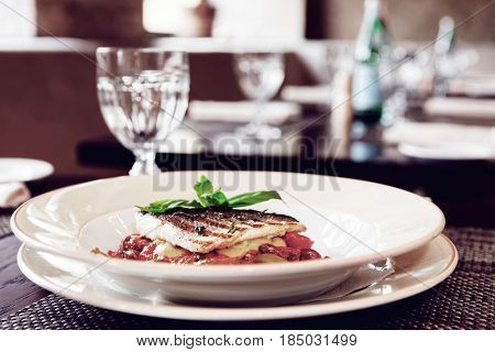 Sea bass fillet with tomato sauce and capers, place setting of a restaurant, toned image