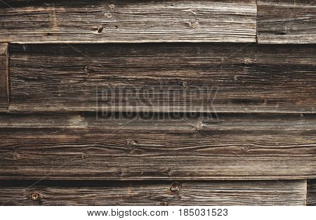 Old wooden surface with cracks and nail holes, dark grunge texture, toned image