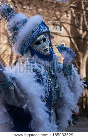 Woman Posing In A Blue Winter Costume And Mask At The Venice Carnival In Venice, Italy