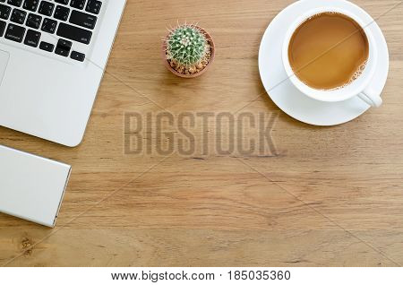 Wooden Desk Table With Computer Laptop, External Hard Disk, Cactus And Cup Of Coffee. Top View With
