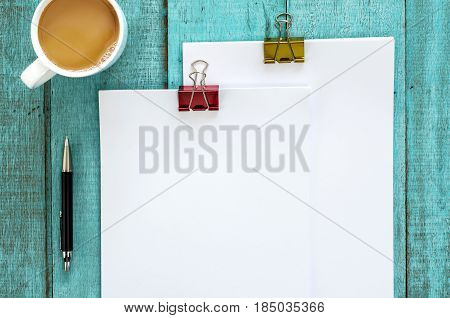 Blue Wooden Desk Table With Paper Reams And Cup Of Coffee.