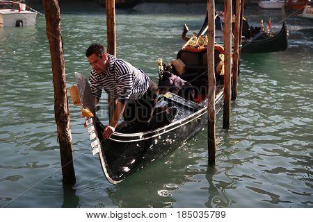Gondolier Polishing His Gondola In Venice, Italy