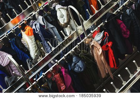 Variety of colored winter and autumn clothes on metal hangers in the wardrobe of a cinema, theater or exhibition. Top view of a large number of different clothes on hangers. Selective focus.