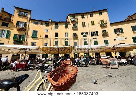 LUCCA ITALY - APRIL 16 2017: Tourists visit the ancient Town square (Piazza dell'Anfiteatro - Amphitheater Square) in the small old Town of Lucca Toscana (Tuscany) Italy Europe