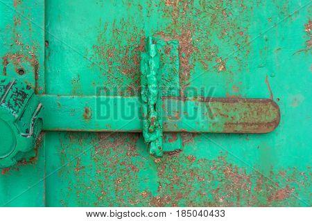Close-up old green door hinge on wooden door.