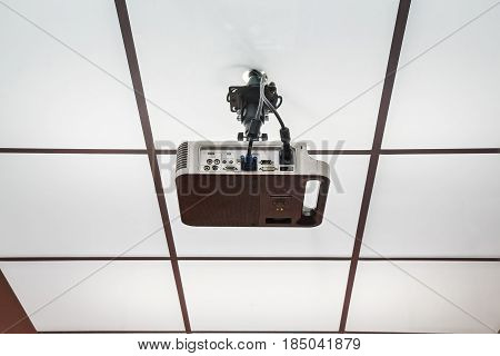 Close up modern multimedia projector hanging on ceiling