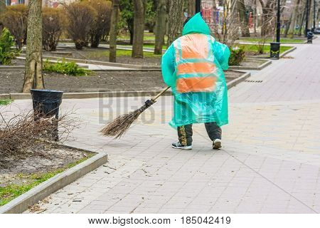 Back view of street sweeper with broom and plastic raincoat