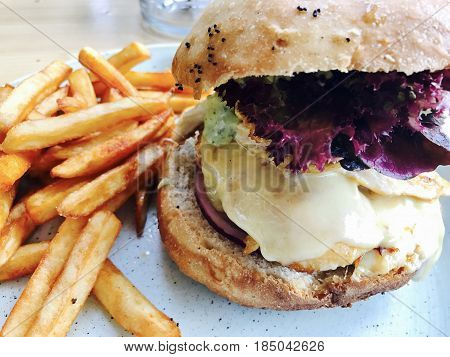 Cheesy chicken burger served in a roll with skinny fries