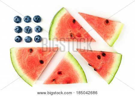 A photo of a representation of the American flag, made up by blueberries and watermelon slices on a white background. A culinary Independence Day greeting card, 4th of July banner