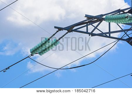 Close up high voltage wire on electricity pylon against blue sky