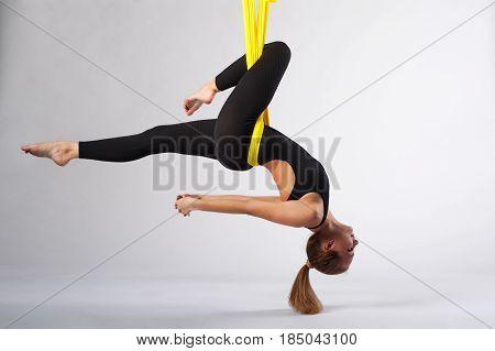 Young flexible woman practicing aerial acrobatics or fly yoga. Fit girl working out in yellow hammock, studio shot. Body balance and antigravity training. Wellness and body care concept.