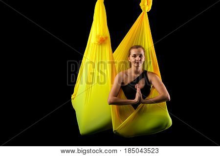 Young relaxed yogi woman meditating in yellow hammock. Blonde girl practicing aerial yoga, studio shot. Body balance and antigravity exercises. Wellness and bodycare concept