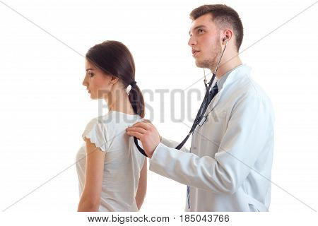 young guy-doctor in white lab coat stethoscope listens back female isolated on a white background