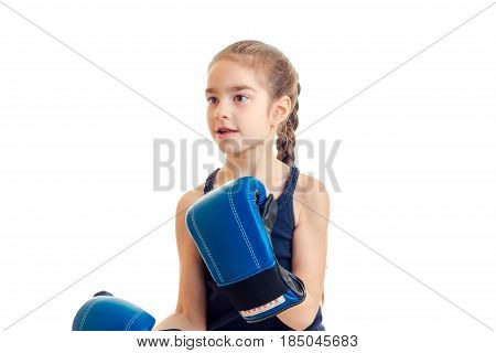 little girl with pigtails in boxing gloves looks toward isolated on white background