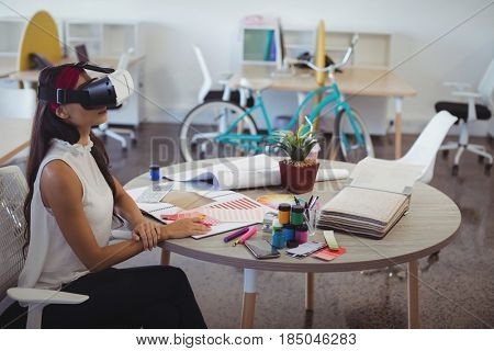 Businesswoman using virtual reality technology while sitting at desk in creative office