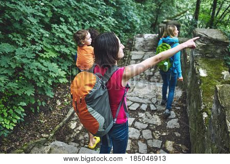 Family with child Hiking In Countryside Wearing Backpacks. A woman with a small backpack on her back shows her hand on something to her friends, Indicates the direction