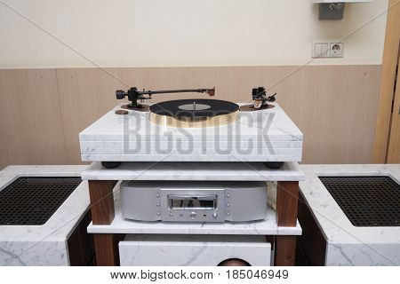 High end turntable on solid stone table in the room