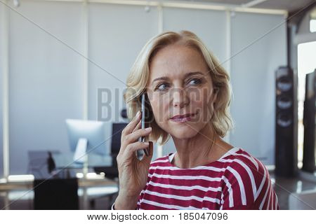Entrepreneur looking away while talking on mobile phone at office