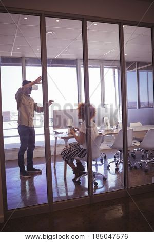 Creative businessman gesturing in front of female colleague while experiencing virtual reality in office
