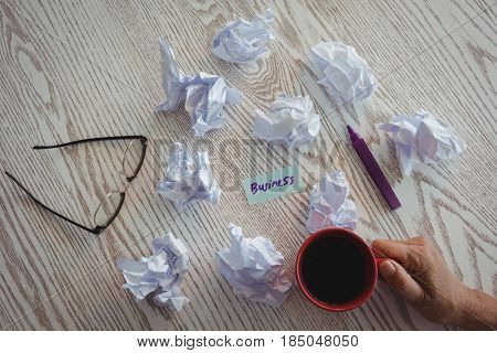 Cropped hand of businesswoman holding coffee cup by crumpled papers on desk in office