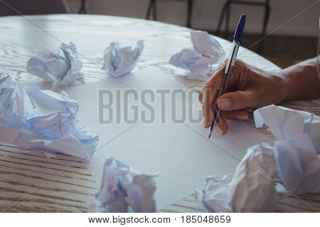 Cropped hand of businesswoman writing amidst crumpled papers on desk