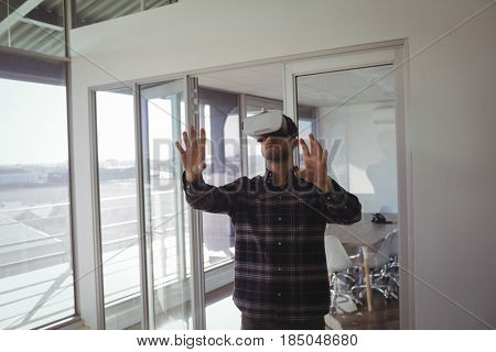 Young businessman gesturing while experiencing virtual reality in office