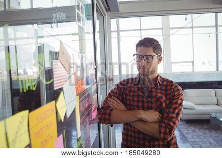 Thoughtful businessman looking at adhesive notes on glass in office