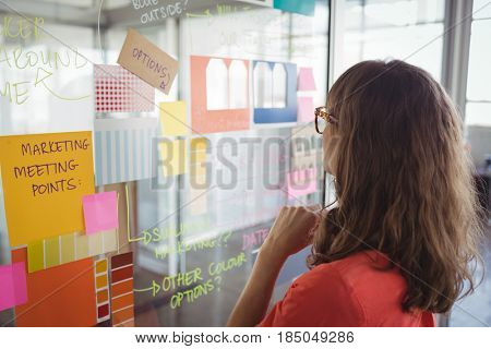 Rear view of businesswoman planning with adhesive notes on glass in office