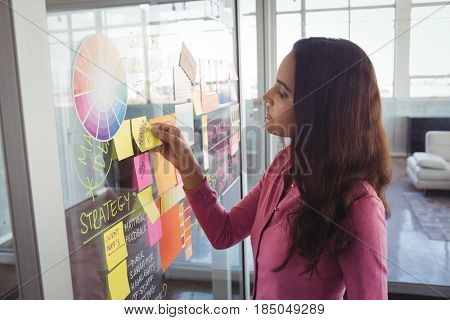 Young female designer removing adhesive note from glass in creative office