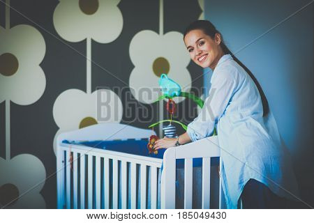 Young woman standing near childrens cot
