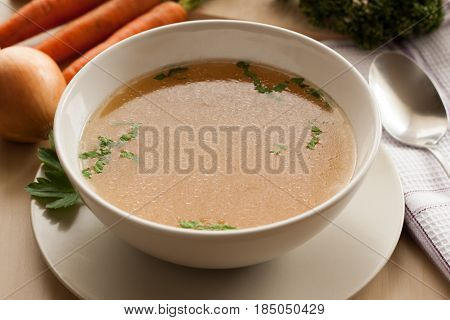 Bone broth made from chicken served in a bowl with parsley